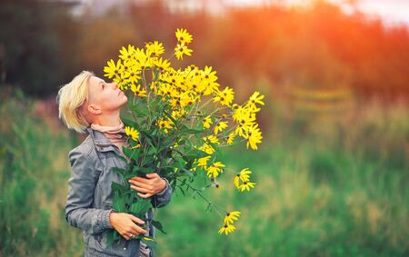 Beautiful blonde woman enjoying flower field, Hipster girl holding a bouquet of wildflowers in her hands, pretty girl relaxing outdoor, having fun, happy young lady spring green nature harmony concept Standard-Bild