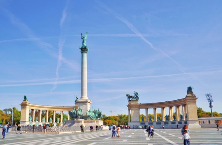 Millennium Monument on the Heroes' Square Hosok Tere under picturesque sky at sunny summer day. Blurred unrecognizable faces of people. One of the most visited attractions squares in Budapest, Hungary