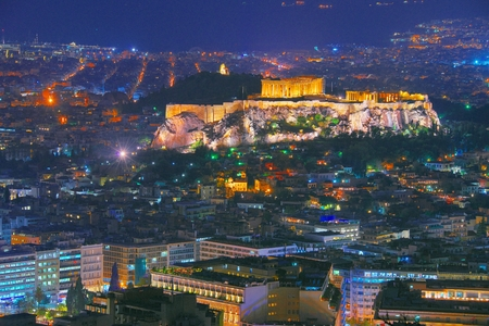 Stadtbild von Athen mit beleuchtetem Akropolis-Hügel, Pathenon und Meer nachts. Skyline von Athen bei Nacht vom Mt. Lykavitos mit Akropolis, Griechenland gesehen. In blauer Stunde geschossen.