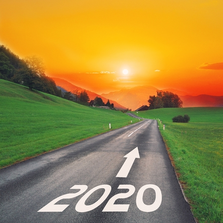 Driving on idyllic open road against the setting sun forward on goals in the mountains to new year 2020. Concept for success, passing time and future. Empty asphalt road.