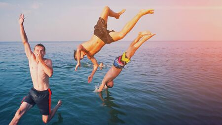Young people jumping inside ocean in summer excursion day. Happy crazy friends diving from sailing boat into the sea. Tropical vacation, youth, travel and fun concept Group of happy people in water