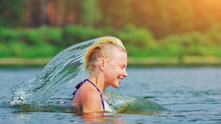 Active young blonde woman splashing water in river. Beautiful healthy lady in water waving hair, relax and laughing, raising head out of the water Vacation in paradise enjoying swimming Motion freeze Standard-Bild