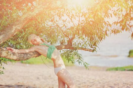 Summer lifestyle portrait of pretty happy young girl with tanned sexy body. Wearing stylish bikini, young girl standing in shade of a tree and enjoy beauty of nature lit by sunlight at hot summer day