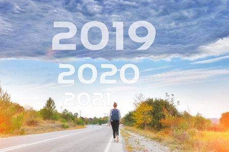 Woman traveler walking alone along road to goals 2020 2021 new year. Danger to 2019 year concept with rainstorm clouds. Success passing time, future concept Empty asphalt road Leaving behind old years