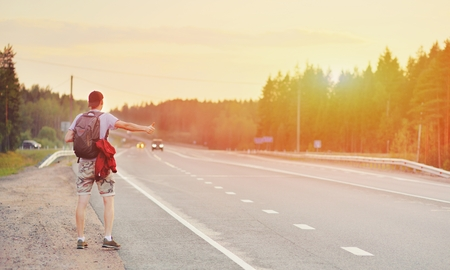 Hitchhiking young traveller man try to catch car on a forest road in sunset. Caucasian tourist guy with backpack stranded and alone on way in nature. World travel road trip, holiday hitch hike concept