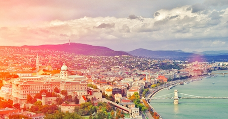 Budapest, Hungary. Beautiful aerial panoramic skyline view of historic Buda Castle Royal Palace and South Rondella with Szechenyi Chain Bridge over River Danube at sunrise with blue sky and clouds