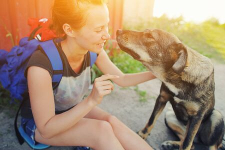 Closeup portrait young hipster woman with backpack kissing dog