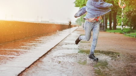 Young happy girl jumping in a puddle on the road under summer rain. Positive funny woman splashing water legs on a rainy day in the city. Feet in shoes or rubber boots. Spring season and rain concept.