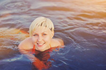Geothermal spa. Happy smiling blonde woman relaxing and swimming in hot spring thermal pool. Girl enjoying bathing in a blue water lagoon Relaxing in a natural bath outdoor Wellness and health concept