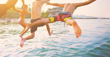 Group of happy crazy people having fun jumping in the sea water from boat. Friends jump in mid air on sunny day summer pool party at diving holiday. Travel vacation, friendship, youth holiday concept. Standard-Bild