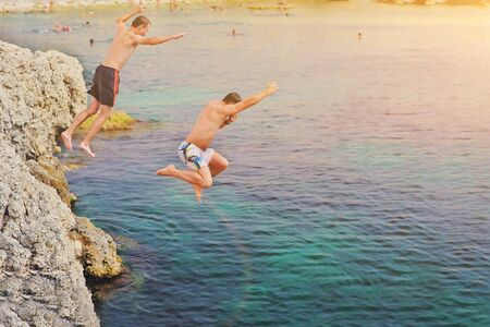 Happy crazy friends jumping inside natural sea pool from rock at sunset. Young fearless two guys people having fun diving inside ocean water from cliff. Summer lifestyle and adventure vacation concept