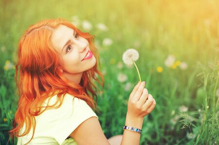 Portrait of young redhair woman blowing dandelion with joy in spring garden. Springtime Beautiful girl at sunset in meadow landscape. Allergic to pollen of flowers. Spring allergy free healthy concept