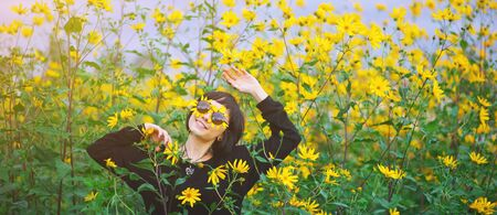 Close up creative portrait of a beautiful young smiling happy brunette girl with yellow flower petals under sunglasses on background of a field of sunflowers. Woman summer lifestyle and healthy teeth Standard-Bild