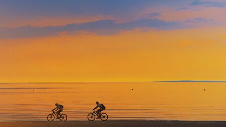 Biker silhouette riding along beach at sunset on bike Sporty company group of friends on bicycle outdoors Success achievement accomplishment and winning concept with cyclist mountain biking. Copyspace