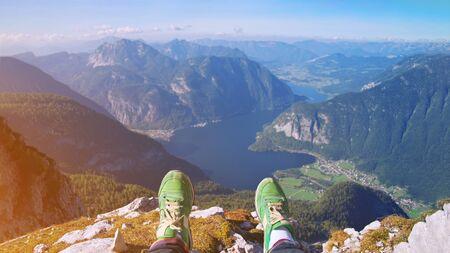 Legs of traveler in stylish green sneakers sitting on a high mountain cliff enjoying scenery mountain top. Pov view Hiking freedom concept Austria Hallstatter See lake Krippenstein mountain Hallstatt