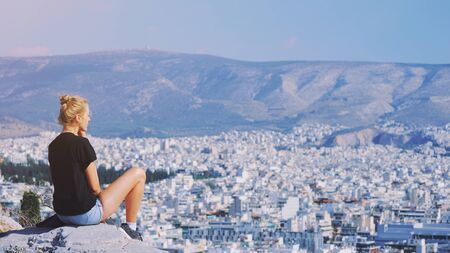 Young tourist woman sitting on top of mountain and looking at a beautiful landscape cityscape Athens Greece. Adult girl tourist relax on hill overlooking Athens in summer. Famous Athen city in Europe