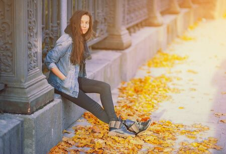 Young pretty hipster woman sitting near iron fence in a trendy denim jacket black jeans and fashion trendy boots. Beautiful millenial girl and yellow golden autumn maple leaves. Fall on city street