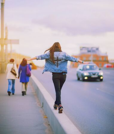 Fearless girl walking on the sidewalk on a busy road, balancing hands. Brave girl in a denim jacket with a cross on back walking on curb near the road and keep balance. Life risk adventure concept