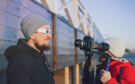 Actor in camera on outdoor winter location. Videographer with gimball video dslr Young professional vlogger videographer shooting outdoor on modern camera. Filming interview vlog behind the scene