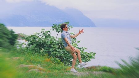 Man suffering from dizziness with difficulty standing up while climbed a mountain. Danger hiking in mountain. Vertigo headache adventure risk concept