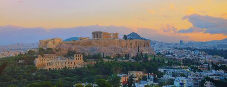 Parthenon temple in Acropolis Hill, Athens, Greece, shot in blue hour over old town during colorful sunset with pink and purple clouds in the sky. Lycabettus Hill on background panorama Europe travel