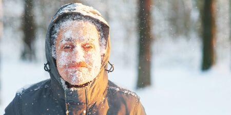 Spaßporträt eines jungen gefrorenen Mannes. Joggen in einem Schneesturm im Wald. Gesicht mit Schnee und Frost bedeckt. Nahaufnahmeporträt des glücklichen jungen Mannes lächelt bei kaltem Wetter im Winterwald bei Sonnenuntergang. Standard-Bild