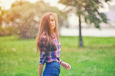 Young happy teen girl with long wavy hair walking under summer rain. Positive funny woman enjoying a spring shower raindrops spray on a rainy day outdoors. Spring season, bad weather and rain concept