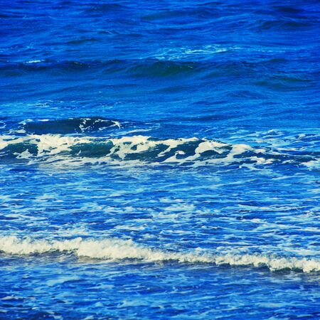 Abstract clean sea background, view on ripple foam surface of water. Deep turquoise blue ocean waves. Calm ocean water background landscape. Clear water wave texture. Marine aqua at tropical summer Stock Photo