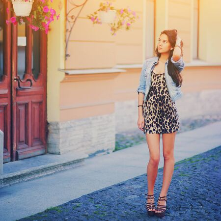 Stylish long hair brunette woman in a leopard animal print dress with legs in brown high heel shoes, denim jacket, street fashion concept. Fashionable girl walking on summer street. Trendy style.