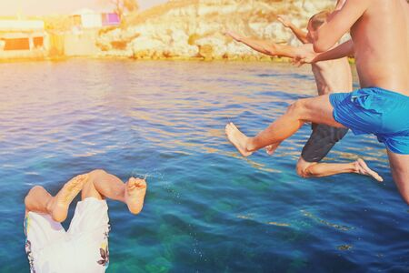 Group of happy crazy people having fun jumping in the sea water from boat. Friends jump in mid air on sunny day summer pool party at diving holiday. Travel vacation, friendship, youth holiday concept 免版税图像