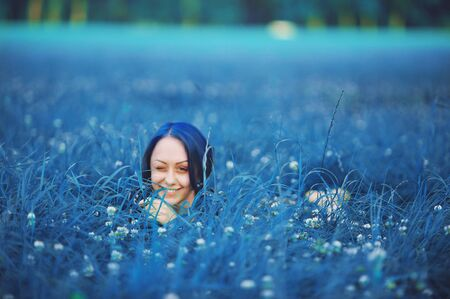 Millennial girl with blue hair. Beautiful young stylish smiling woman lying down and winks on grass in summer time in the park. Fresh natural summer peace view. Classic blue 2020 year color concept