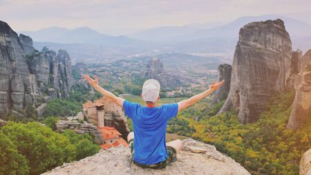 Man rise hand up sitting on top of mountain enjoying peaceful mountain landscape. Belief, praise, religion and worship. Freedom meditation and travel concept. Monastery Meteora Kalambaka in Greece