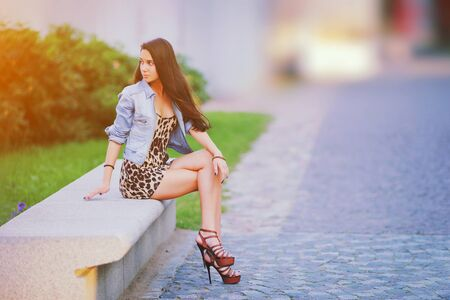 Stylish long hair brunette woman in a leopard animal print dress with sexy legs in brown high heel shoes, denim jacket, street fashion concept. Fashionable girl sitting on summer bench. Trendy style.