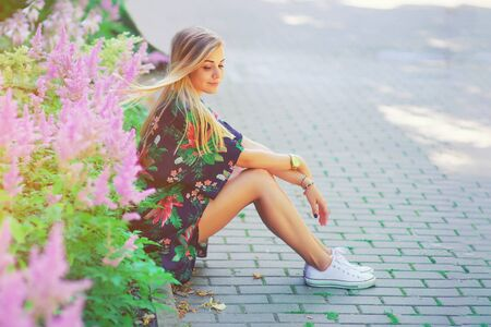 Portrait of beautiful young girl in colorful boho vintage dress sitting near colorful flowers. Romantic woman with blowing long hair in nature outdoor. Pretty happy tenderness model summer lifestyle