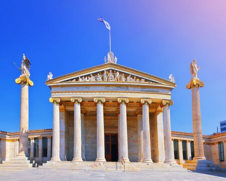 National Academy of ancient Athens neoclassical building with Athena and Apollo statues. Iconic neoclassic Greek Academy of Athens. Landmark in historic center of Attica, Greece national flag, Europe