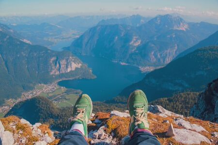 Legs of traveler in stylish green sneakers sitting on a high mountain cliff enjoying scenery mountain top. Pov view Hiking freedom concept Austria Hallstatter See lake Krippenstein mountain Hallstatt