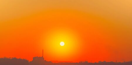 Heatwave hot sun. Global warming llimate change. Summer background with a magnificent summer sun. Autumn sunset. The setting sun in a clear sky. Hot city weather concept. High temperature at summer Standard-Bild