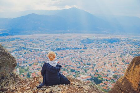 Young woman sitting on top of cliff in summer mountains at sunset and enjoying beautiful view of nature landscape cityscape. Monastery Meteora Kalambaka town in Greece Europe. Wanderlust adventure