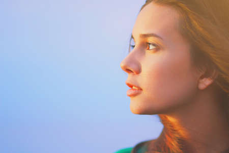 Beautiful young woman relaxing and enjoying sun at sunset. Beauty sunshine girl side profile portrait. Pretty happy lady enjoying summer outdoors. Positive emotion life success mind peace concept Imagens