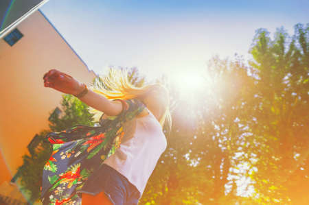 Attractive happy young woman in white t shirt flying hair enjoying her free time at sunset outdoor. Beauty blonde girl portrait at summer. Freedom lifestyle springtime concept. Sun glow on background Imagens