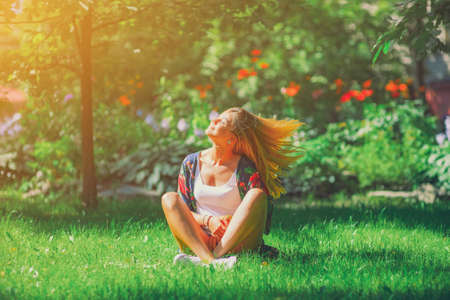 Happy free young woman sitting in yoga position with eyes on summer park grass outdoors Imagens