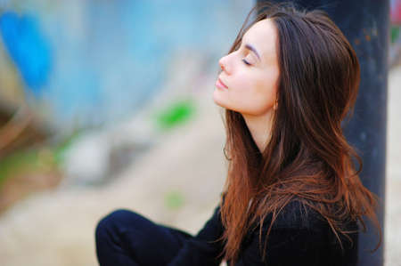Portrait of a dreamy cute happy woman worker meditating outdoors with big eyes closed, sitting with the effect of blur closeup. De stress relief fit exercise, easy train enjoy career rest time concept Foto de archivo