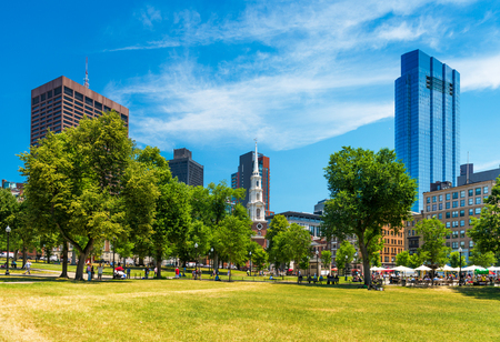 boston common: Boston, MA - July 2016, USA: People sitting on grass and walking around in Boston Common Park, view on Skyscrapers and Park street Church
