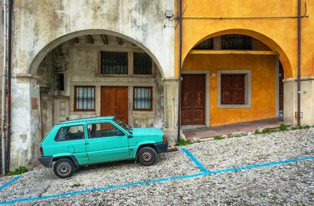 veneto: Vittorio Veneto (Veneto region) - December 2015, Italy: Green car parked by old italian house