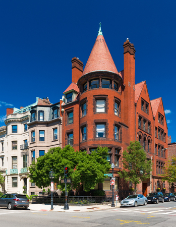 brownstone: Boston, MA - July 2016, USA: Old historical building made of red brick and brownstone with cone rooftop in Boston back Bay district, against the backdrop of a clear blue sky