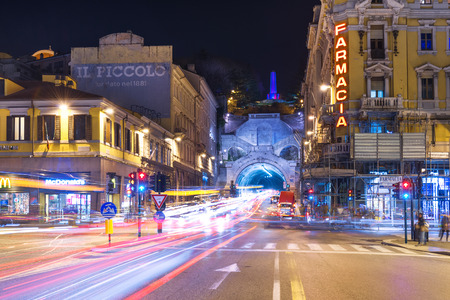 Trieste, Friuli Venezia Giulia region - March 2015, Italy: Night view of the city of Trieste with car traffic lights trails, Pharmacy store and McDonalds building on Piazza Carlo Goldoni. Editorial