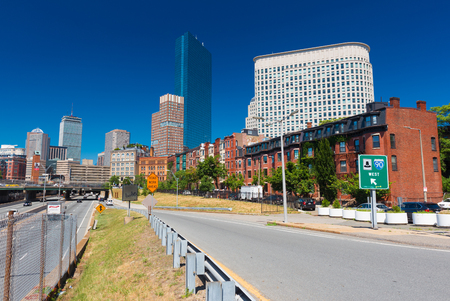 hancock: Boston - June 2016, USA: The street of Boston, view of John Hancock Tower, surrounding buildings and exit to the highway, cityscape against the blue sky