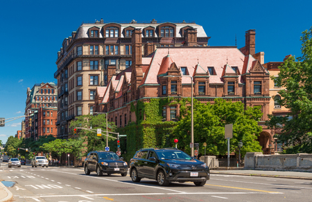 Boston, MA - June 2016, USA: Street view with historical houses made of brown stone and cars moving in Back Bay district of Boston