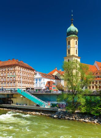 Graz - May 2017, Styria region, Austria: View of the old city center. Franciscan Church, old historical buildings with orange roofs against the clear blue sky. Flowing river Mur Editorial