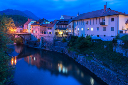 Skofja Loka - April 2015, Slovenia: Night view of the old historic houses and stone bridge reflected in water, old town center in Skofja Loka